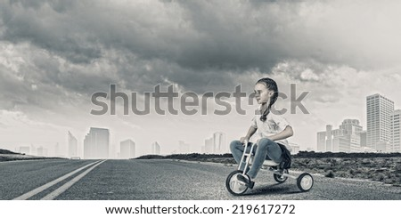 Little cute girl of preschool age riding tricycle