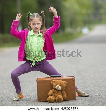 Little cute girl on the road with a suitcase and a Teddy bear. - stock photo