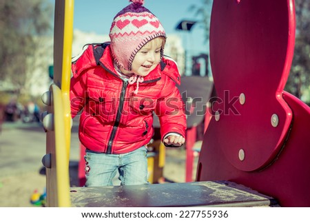 little cute girl playing at the playground in autumn - stock photo