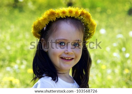 Little cute girl playing in the meadow with dandelions