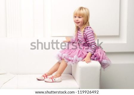 Little cute girl posing happily on sofa - stock photo