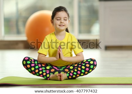 Little cute girl practicing yoga pose on a mat indoor - stock photo
