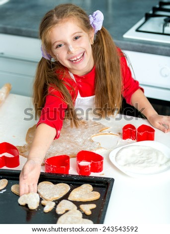 little cute girl puts on baking cookies