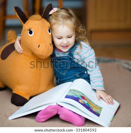 Little cute girl reading book - stock photo