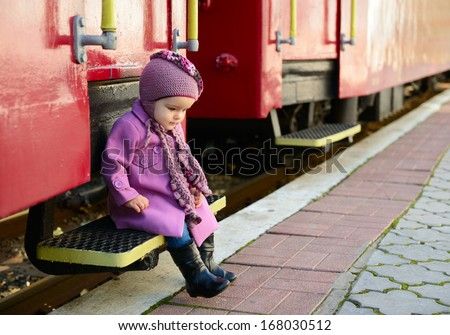 Little cute girl ready to vacation on railway station, baby girl fashion model go on travels - stock photo