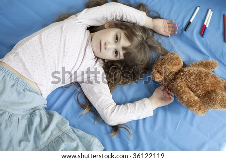 little cute girl seven years old lying on bed - stock photo