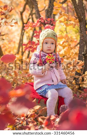 Little cute girl sitting in the autumn forest