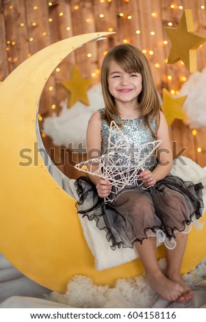Little cute girl sitting on a wooden month with a decorative star in her hands. Children's photozone.