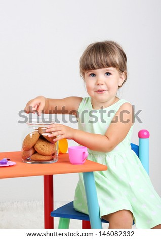 Little cute girl sitting on little chair near table and eating tasty cookie, on gray background