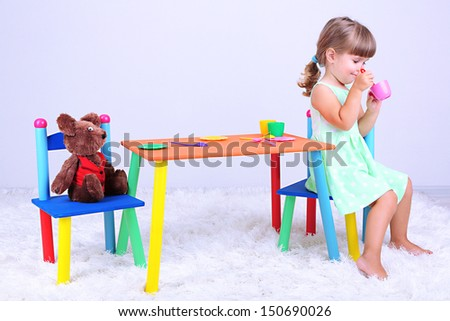 Little cute girl sitting on little chair near table, on gray background