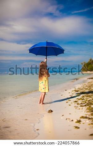 Little cute girl with blue umbrella walking on tropical beach - stock photo