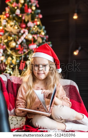 Little cute girl with book near christmas tree