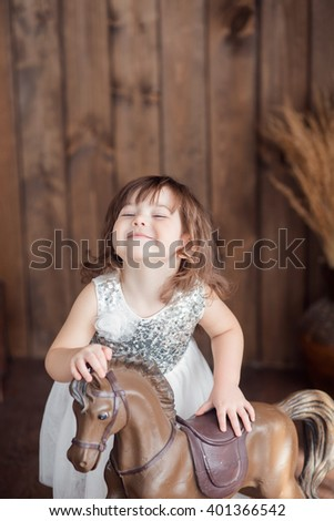 little cute girl with brown hair in a white dress standing on the floor and petting a horse rocking chair, look at the camera, building faces - stock photo