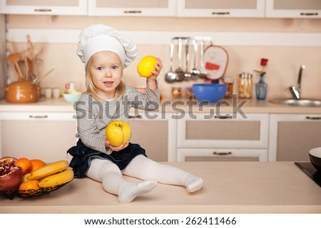 Little cute girl with chef hat holding fruits while cooking. Kitchen interior. Concept for young kitchen hands - stock photo