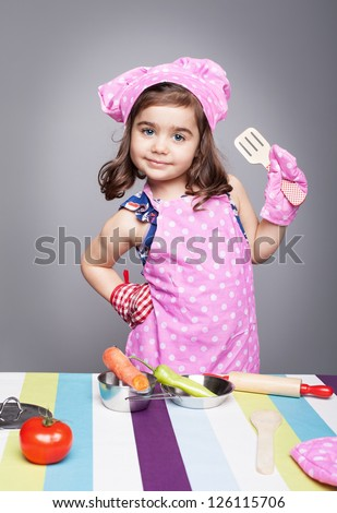 little cute girl with chef uniform posing like a professional model and looking at camera on grey background - stock photo