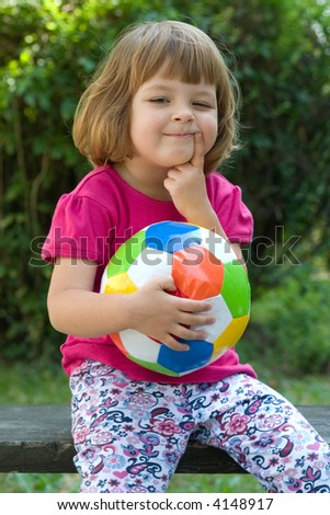 little, cute girl with colorful football outdoors