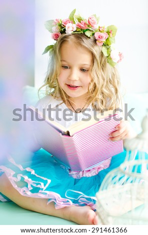 little cute girl with curly hair covered with wreath reading book indoors