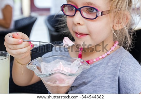 Little cute girl with glasses is eating ice cream at pastry shop in summertime. - stock photo