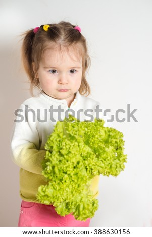 Little cute girl with green fresh salad on the white background - stock photo