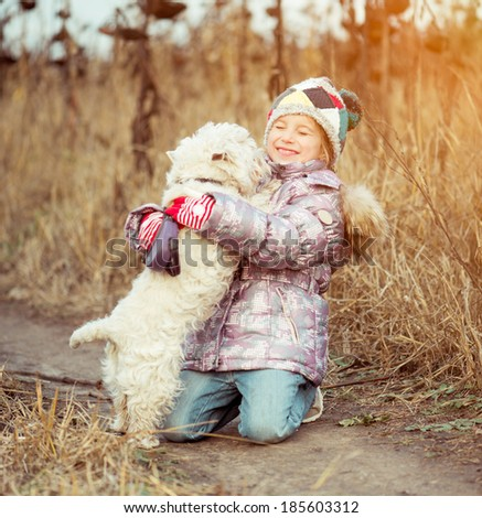 little cute girl with her dog  walking in a field in autumn - stock photo