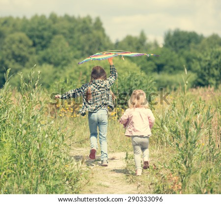 little cute girls flying a kite in a meadow on a sunny day, back view - stock photo