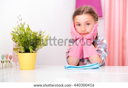 little cute kid bored cleaning up room - stock photo