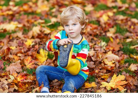 Little cute kid boy in autumn leaves in colorful clothing. Happy siblings having fun in autumn park on warm day. - stock photo