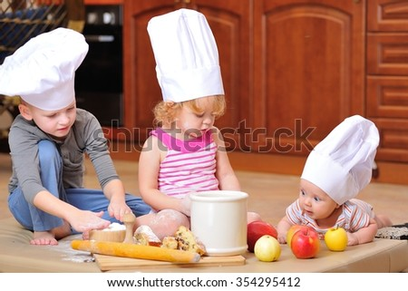 Little cute kids in chef's hats sitting on the kitchen floor, heavily soiled with wheat flour they are playing cook and having fun and next to them a newborn baby also in a chef's hat