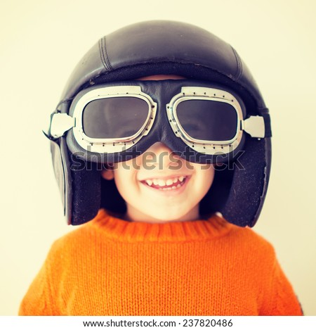 Little cute playful baby kid with pilot hat and goggles ready for airplane flying - stock photo