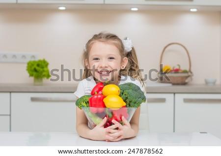 Little cute preschool girl in the kitchen smiles and hugs bowl full of healthy fresh vegetables - broccoli, paprika, lemons - stock photo