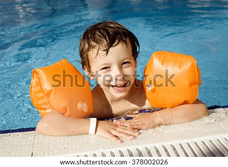 little cute real boy in swimming pool close up smiling - stock photo