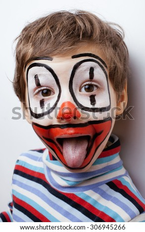 little cute real boy with facepaint like clown, pantomimic expressions close up - stock photo