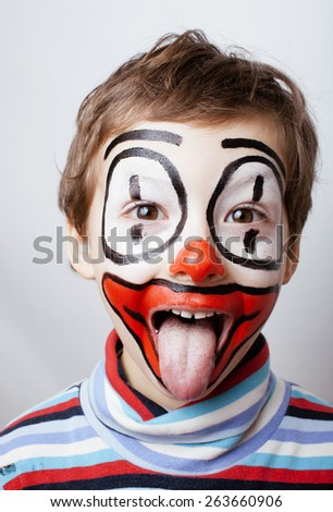 little cute real boy with facepaint like clown, pantomimic expressions close up adorable - stock photo