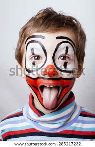 little cute real boy with facepaint like clown, pantomimic expressions close up adorable face - stock photo