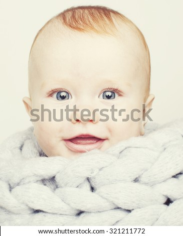 little cute red head baby in scarf all over him close up isolated, adorable kid smiling - stock photo