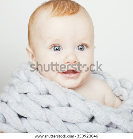 little cute red head baby in scarf all over him close up isolated, adorable kid smiling. winter post card - stock photo