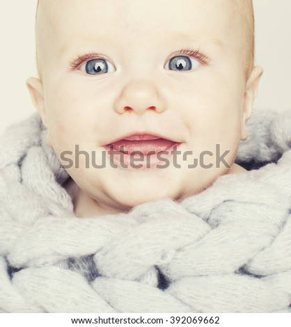 little cute red head baby in scarf all over him close up isolated, adorable kid winter cold - stock photo