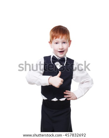 Little cute redhead boy in vest with bow tie shows thumb up. Portrait of well-dressed child in bow tie, approval,, satisfaction gesture. Kid isolated on white background