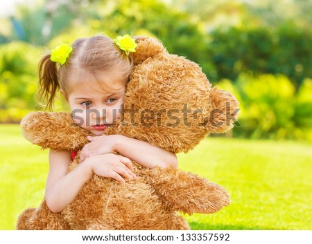 Little cute sad girl holding in hands brown teddy bear, upset child spending time outdoors in spring time - stock photo