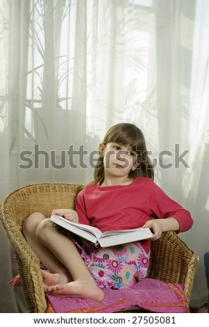 little cute serious girl seven years old reading book sitting in chair