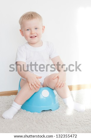 little cute smiling boy on blue potty. have toilet - stock photo