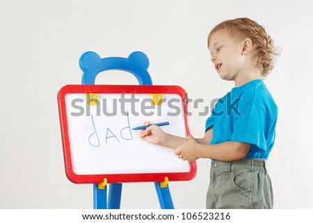 Little cute smiling boy wrote the word dad on whiteboard - stock photo