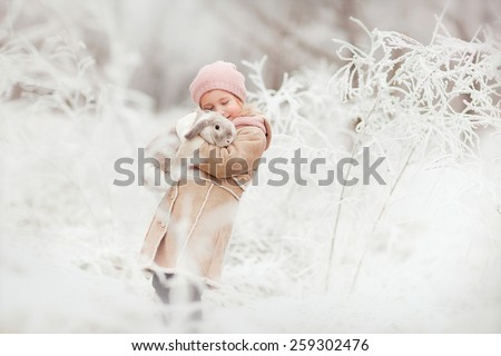 little cute smiling girl in pink hat and beige coat standing in the winter magic forest and holding a rabbit in her hands  - stock photo