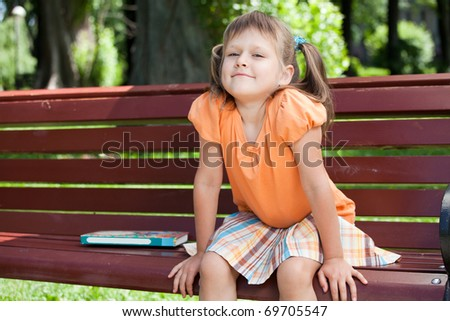 Little cute smiling girl preschooler with open book who is sitting on the wooden bench in summer park - stock photo
