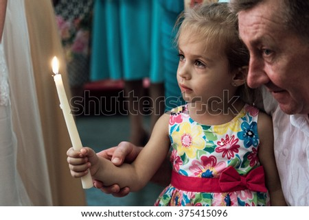 little cute sweet girl holding candle at wedding ceremony in church - stock photo