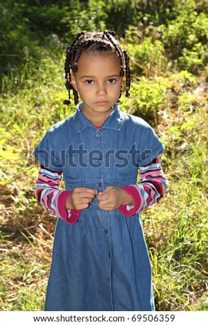 Little dark-skinned girl with tears in his eyes outdoors - stock photo
