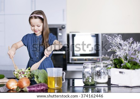little daughter cooking in the kitchen at home. Girl Assisting In Preparing Food - Stock image - stock photo