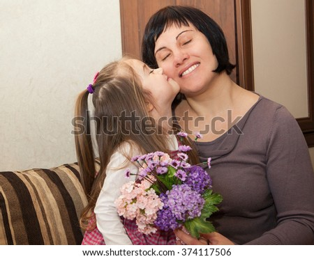 little daughter gives her mother a bouquet of flowers on Mother's Day - stock photo
