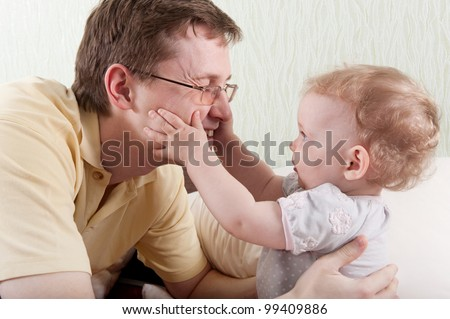 Little daughter touching her fathers face - stock photo