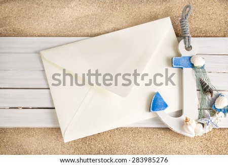 Little decorative anchor and envelope on a wooden planks over sandy background. - stock photo